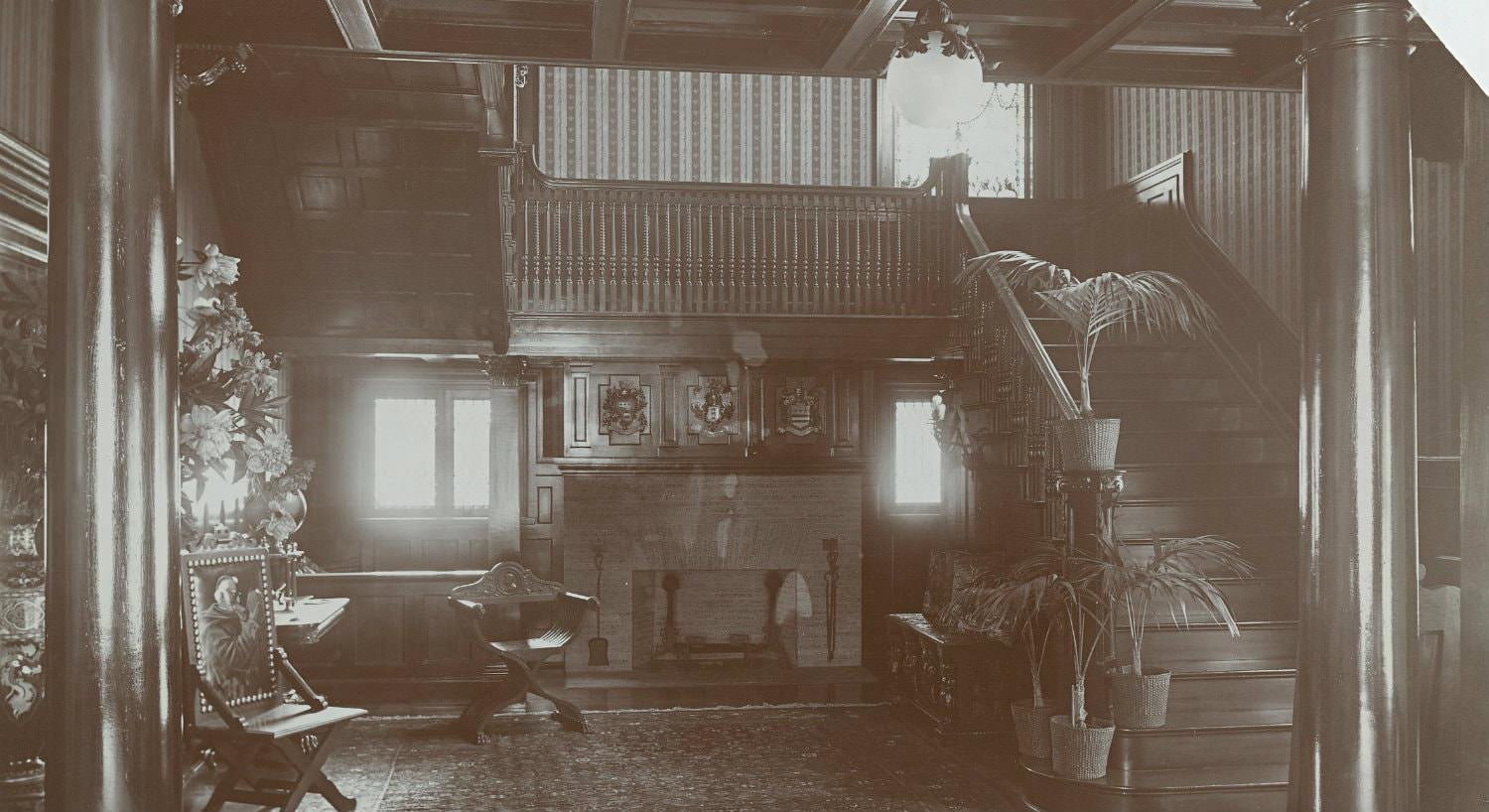 Old black and white photo of common area, fireplace flanked by windows and wood staircase and landing with balcony