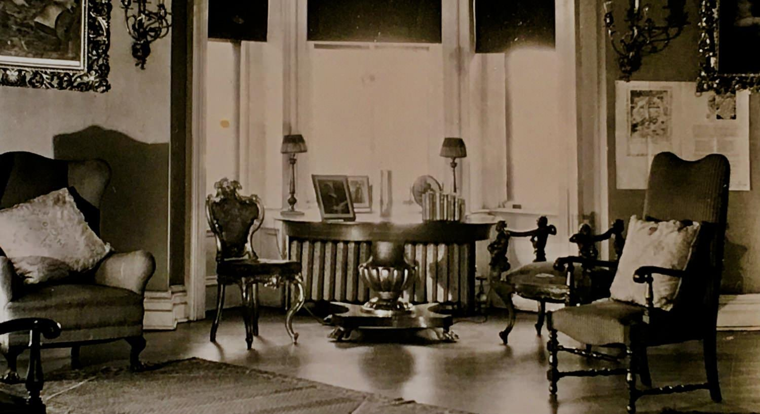 Old black and white photo of round table and chairs in front of bay window