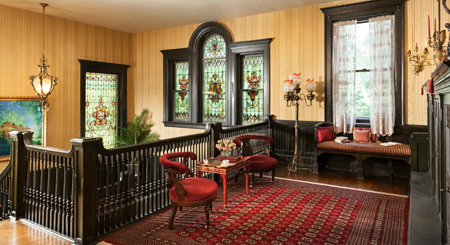 Upstairs balcony with dark wood trim, stained glass windows, red area rug with two velvet and wood chairs