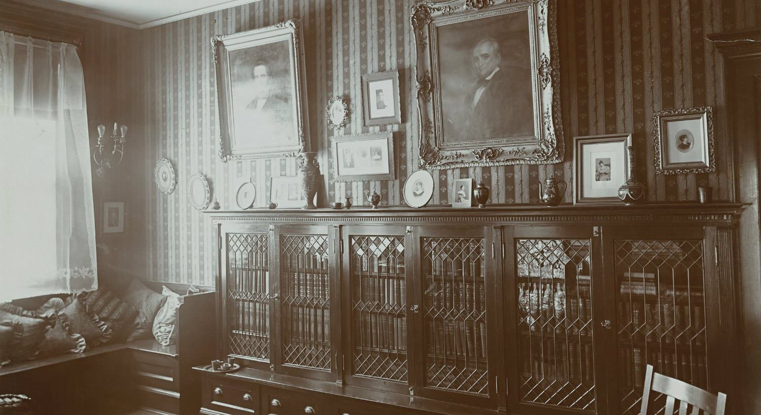 Old black and white photo of library bookcases with glass doors and elaborately framed portraits