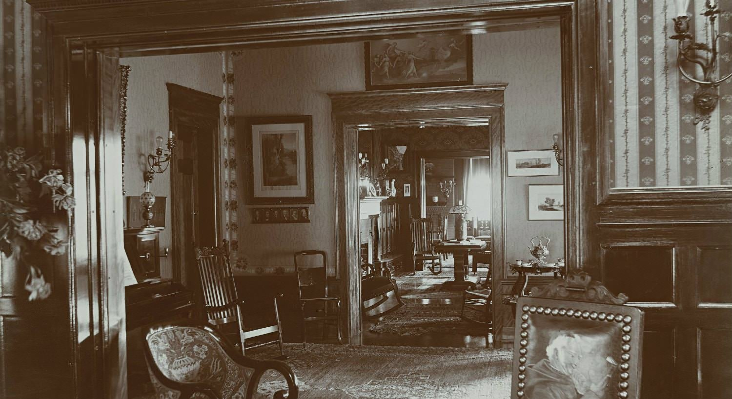Old black and white photo of three connecting rooms with wide wood trim, wood floors, sconce lighting and wood furniture