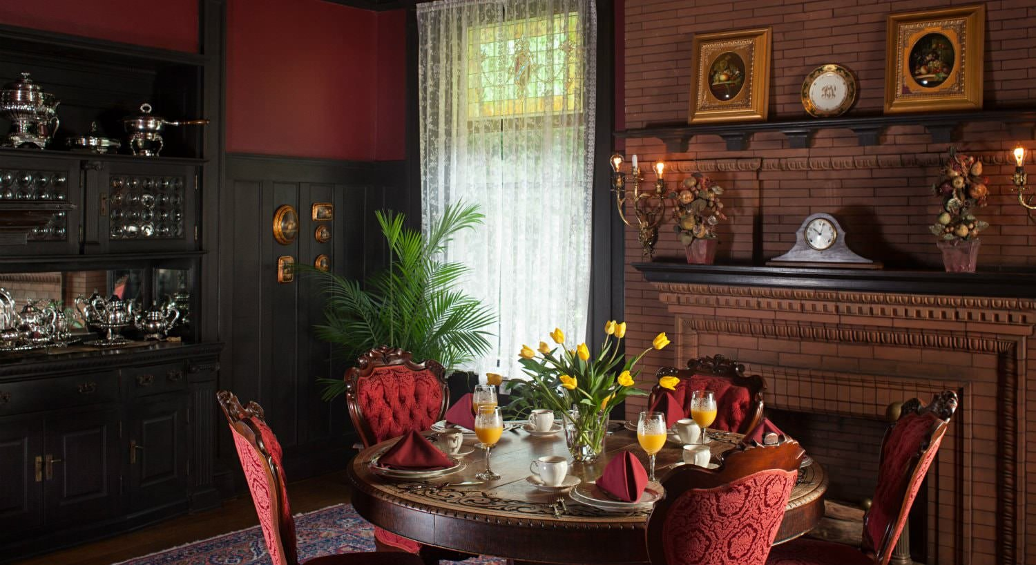 Dining room with red walls, dark wood trim, brick fireplace, and a round carved table with five red velvet chairs