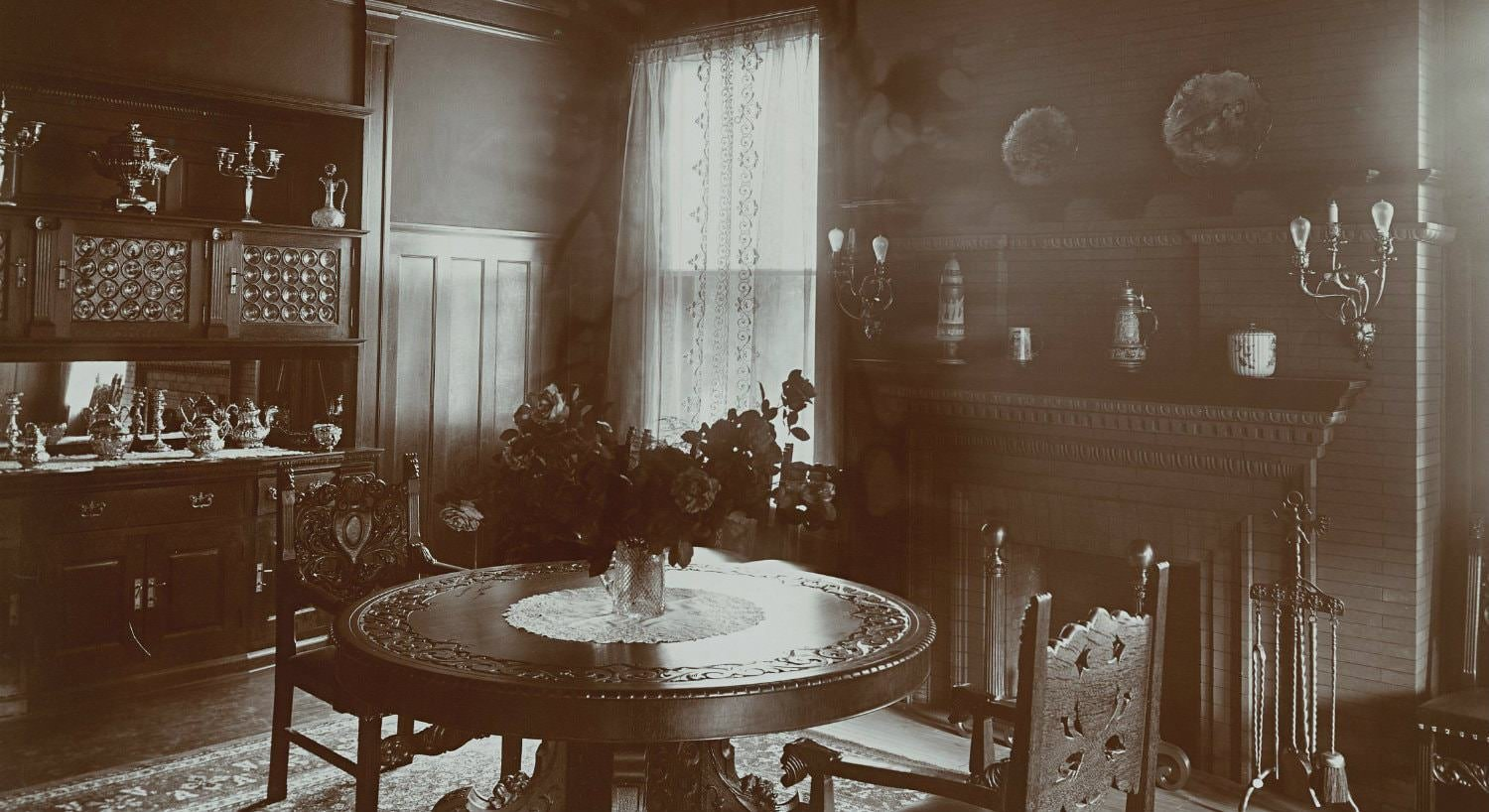 Old black and white photo of dining room with wood trim, brick fireplace, and elaborately carved round wood table and chairs