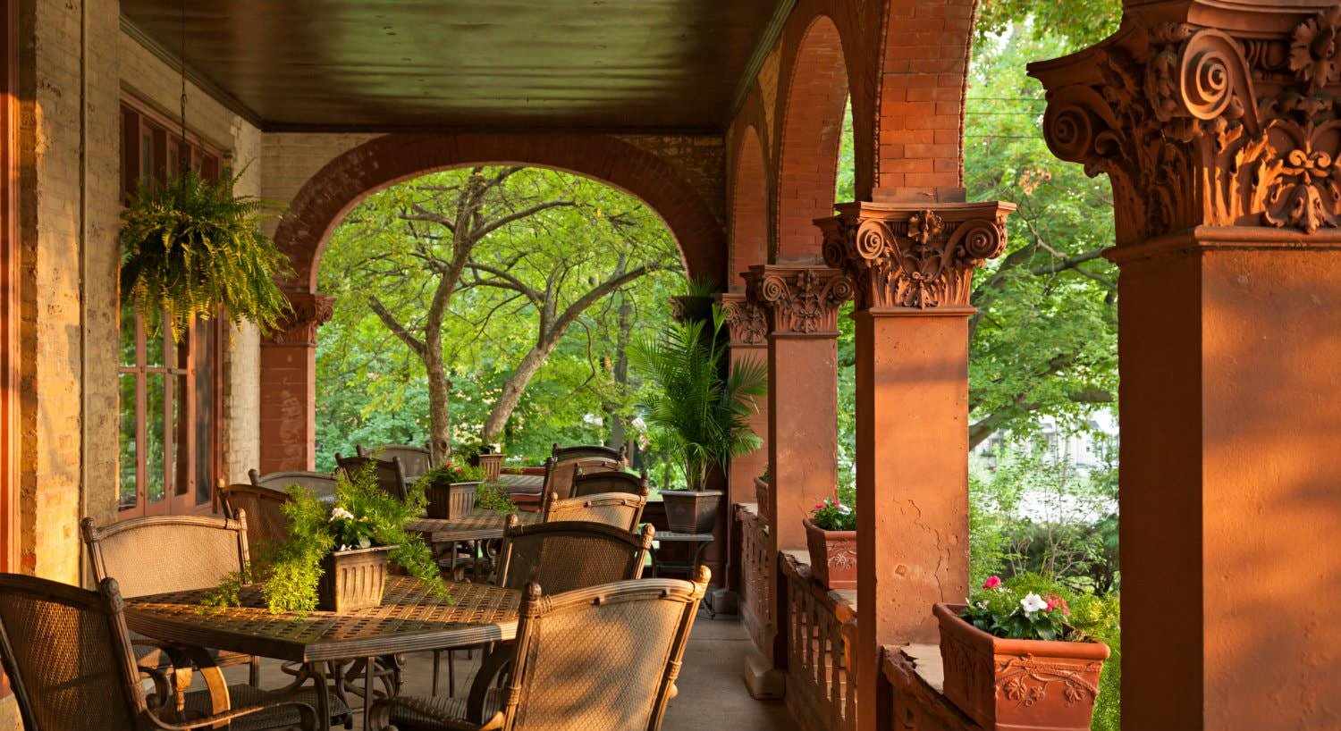 Covered porch with wide arched openings and thick reddish carved posts, and several patio tables and chairs