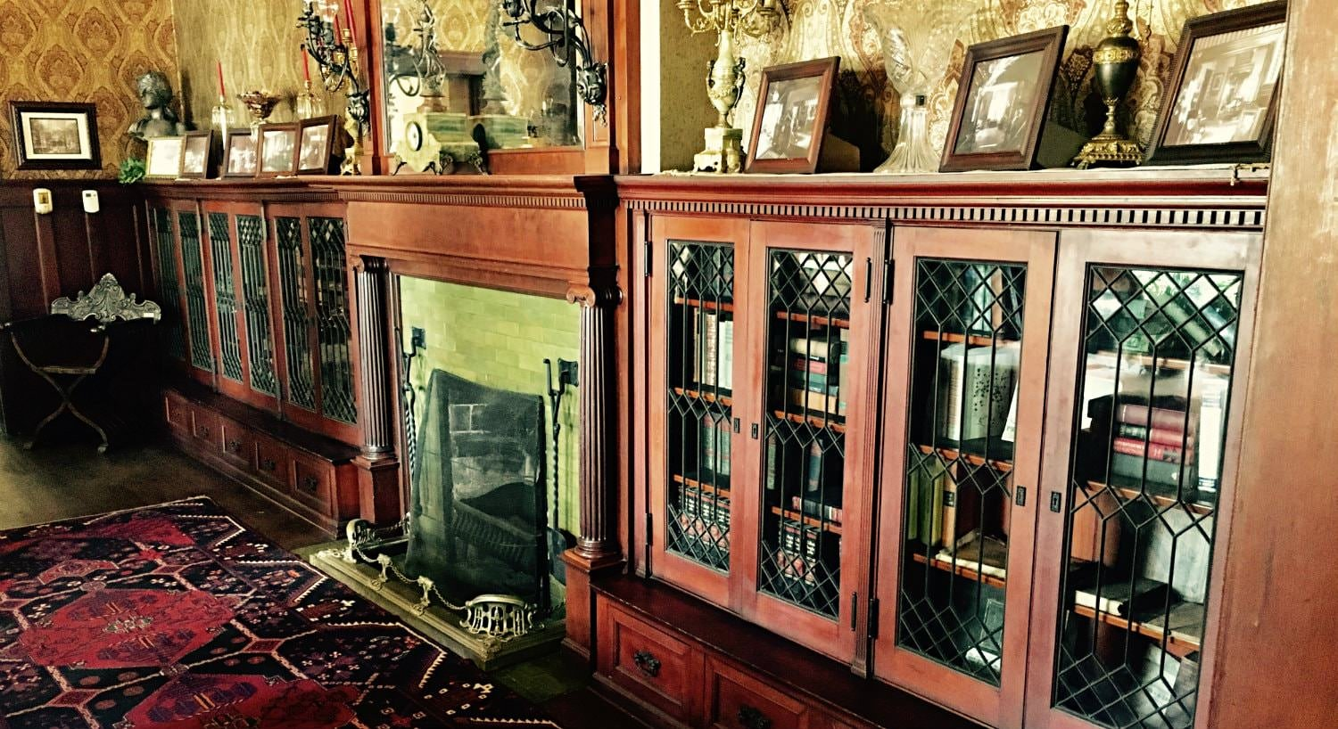 Fireplace flanked by mantel-high bookcases with leaded glass doors and topped with framed photos
