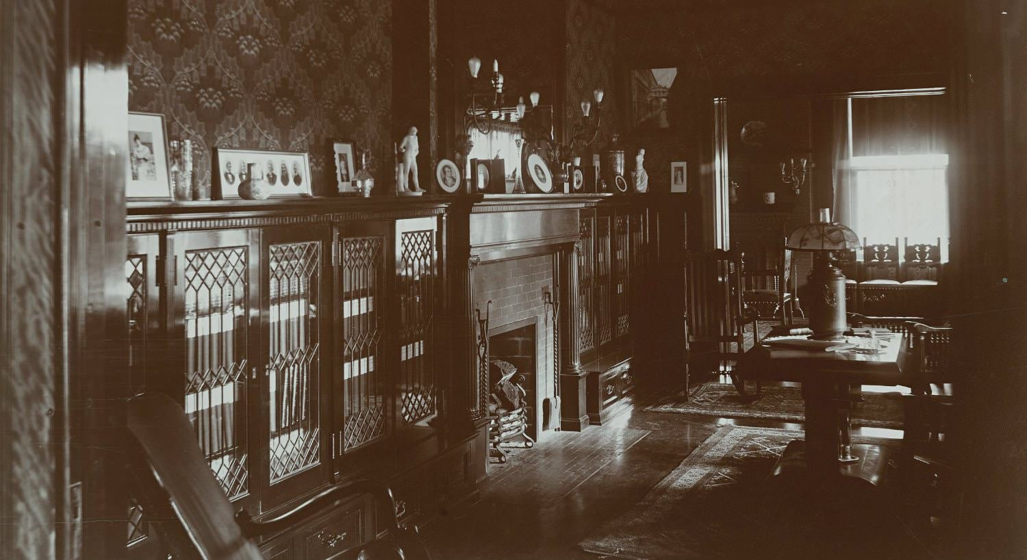 Old black and white photograph of library fireplace flanked by bookcases with leaded glass doors and topped with framed photos