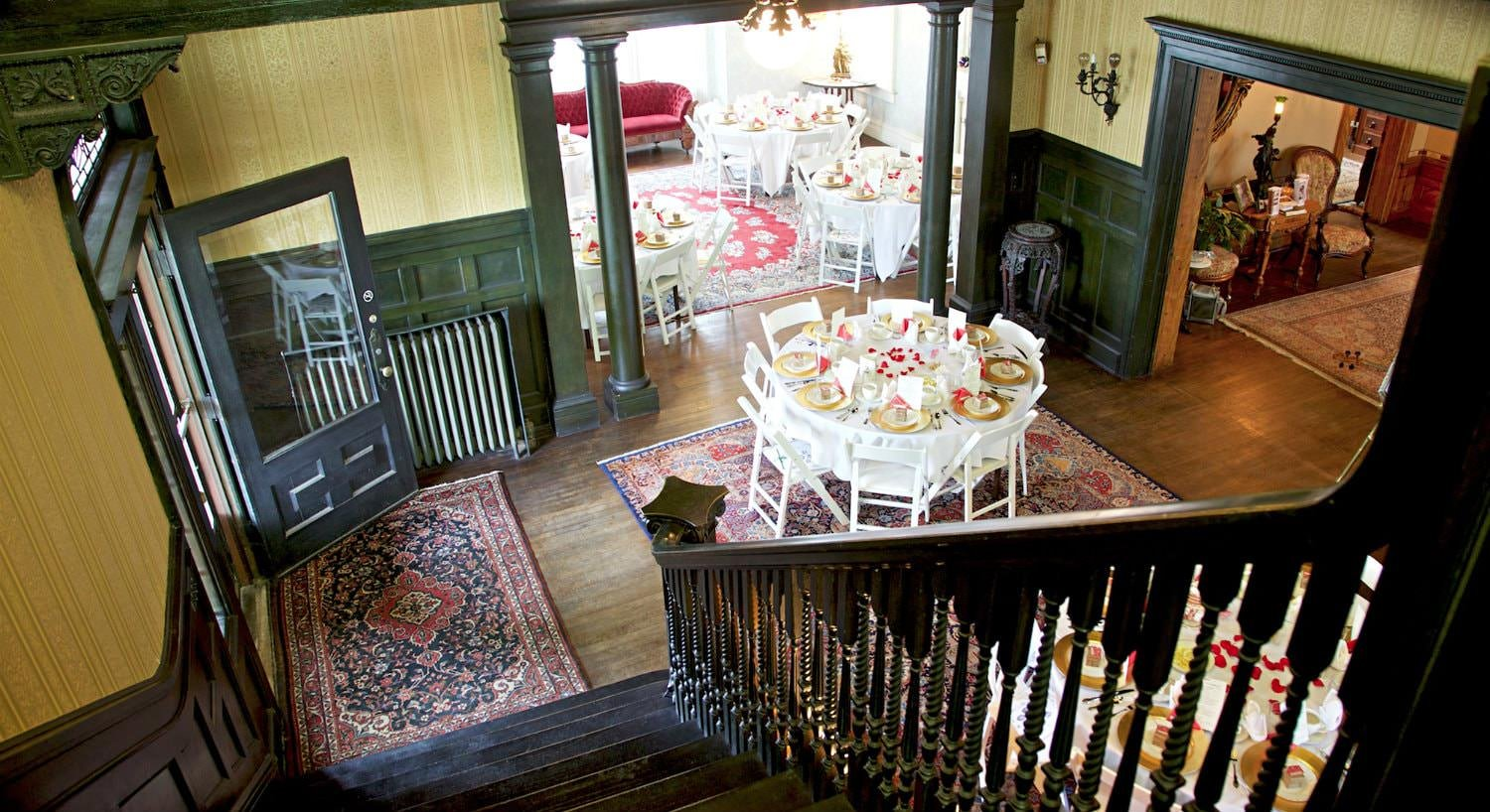 View from top of stairs looking at adjoining rooms with several white round table and chairs set for a meal