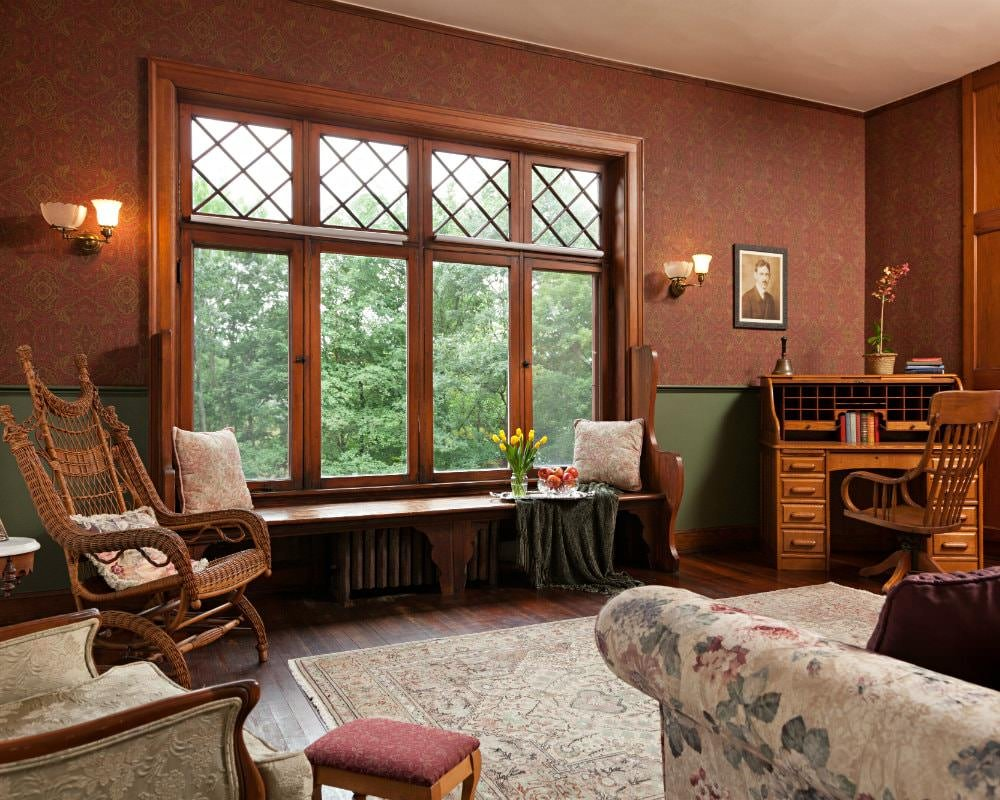 Room with red papered walls, large window with wood bench, sconce lighting, wood floors, chairs, and roll-top desk