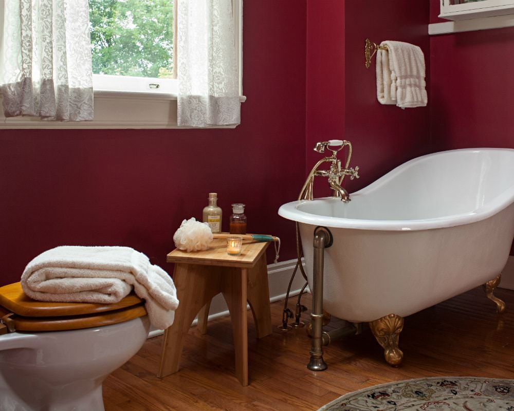 Red bathroom with white trim and curtains, white clawfoot tub and towels and wood bench with toiletries