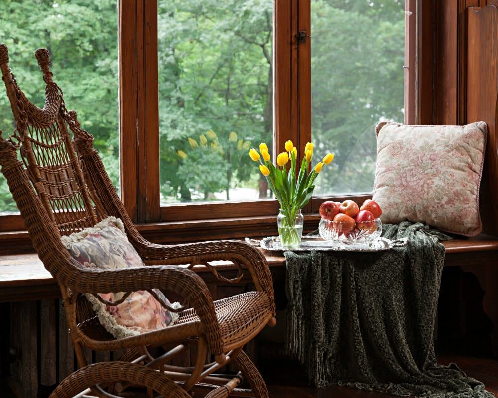 Wood window seat with a tray of fresh red apples and yellow tulips and a green chenille throw blank