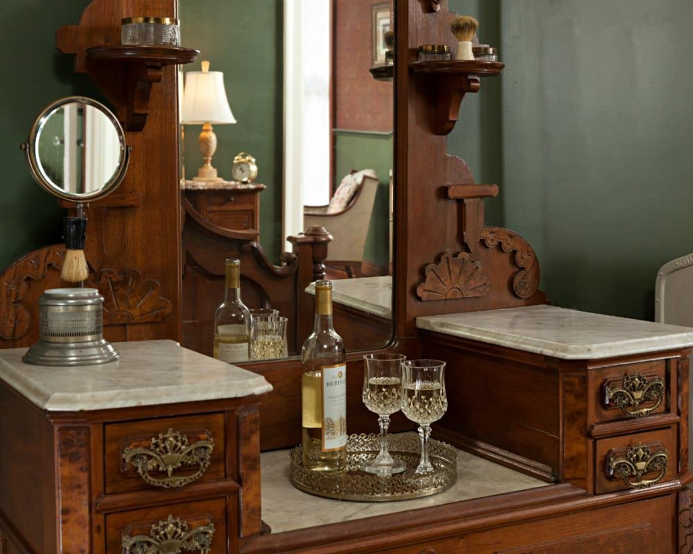 Wood and marble dressing table with mirror with a metal tray topped with white and wine and two wine glasses