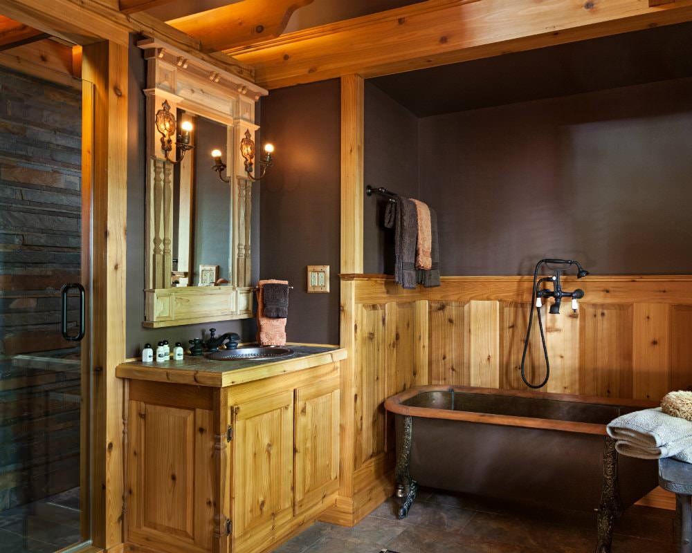 Rustic bathroom with pine woodwork, brown walls, stone walk-in shower with glass door and clawfoot tub