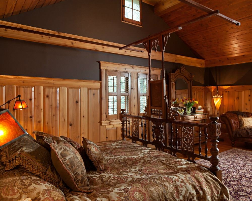 Rustic vaulted room with brown walls, light pine ceiling, paneling and floors and large bed with floral bedding