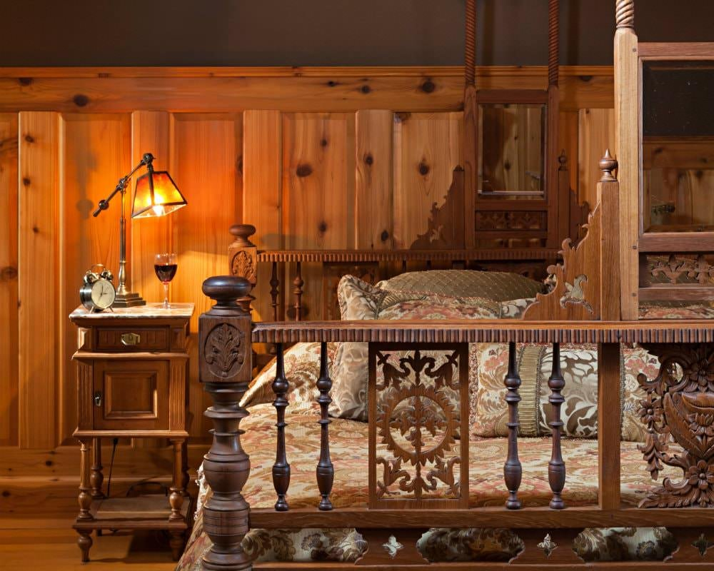 Large bed with carved wood head and footboards, floral bedding and nightstand topped with lamp with amber shade