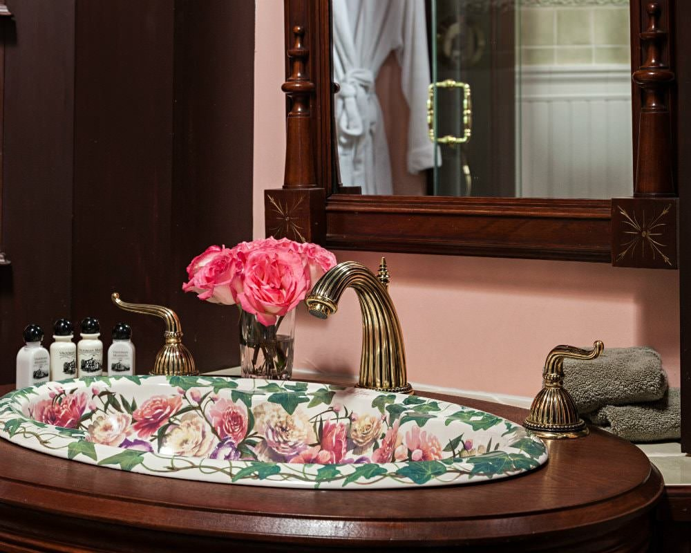 Close-up view of painted floral vanity sink with antique brass faucet, fresh roses, and wood framed mirror