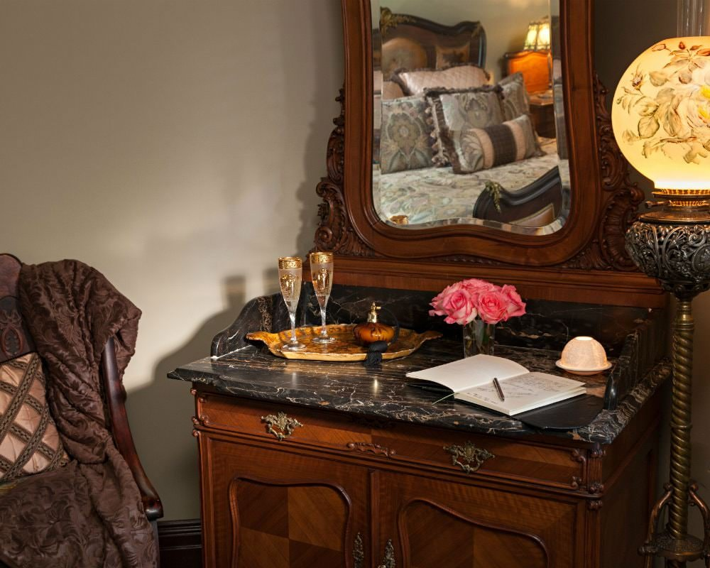 Close-up view of wood and marble dresser with mirror, two champagne flutes, fresh roses, and a journal and pen