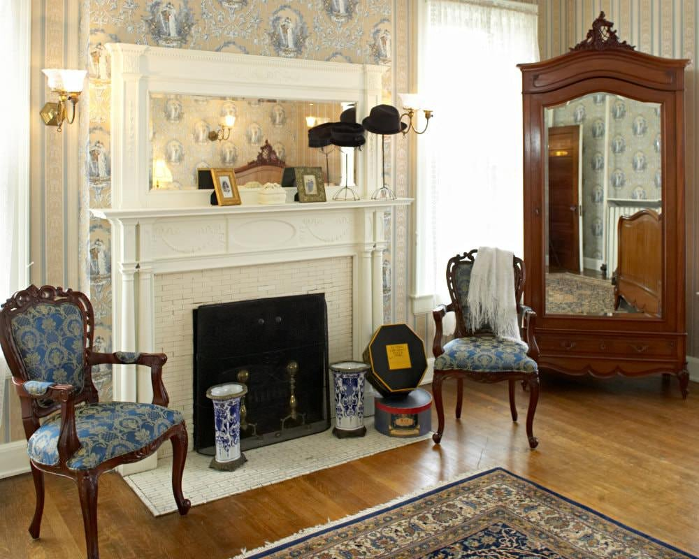 Elegant room with blue and beige wallpaper, lace curtains, white fireplace flanked by wood chairs with blue upholstery