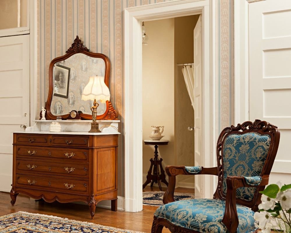 Blue and beige papered walls, white trim and doors, wood and marble dresser with mirror, wood chair with blue upholstery