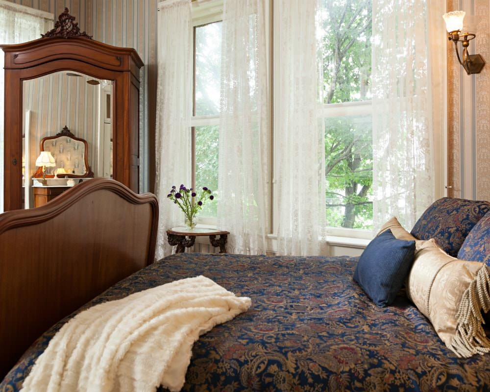 Room with blue and beige striped wallpaper, bed with navy and gold bedding, mirrored cabinet and windows with lace curtains
