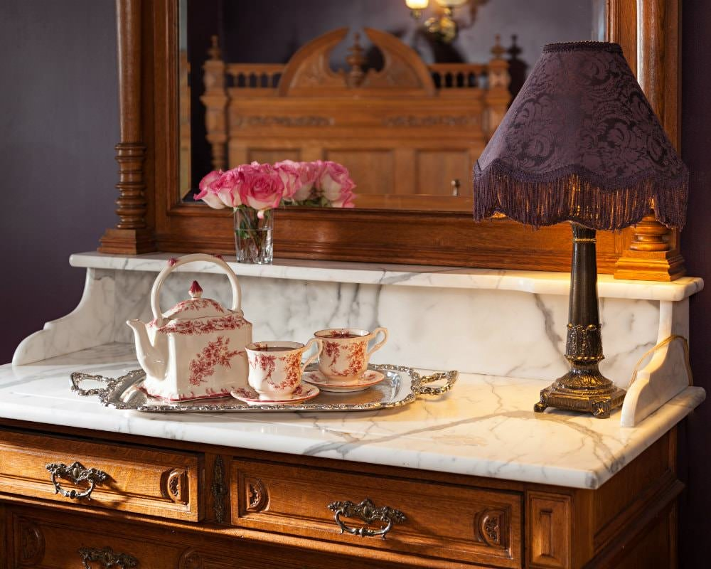 A silver platter with red and white tea set sitting on a wood and marble dresser with mirror