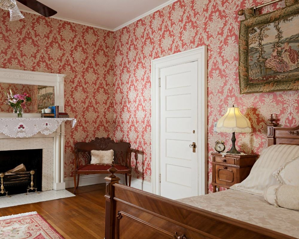 Room with red and ivory papered walls, white trim and doors, wood floors, fireplace and bed with ivory bedding