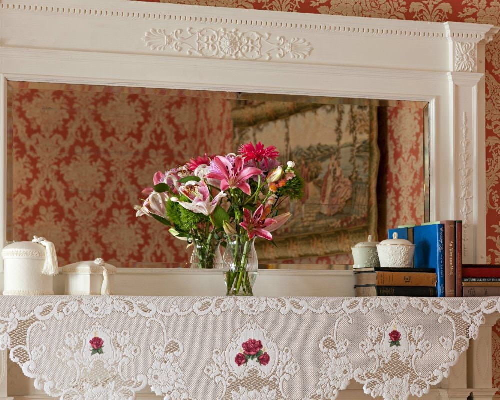 Close-up view of white mantel topped with lace, fresh flowers, and books