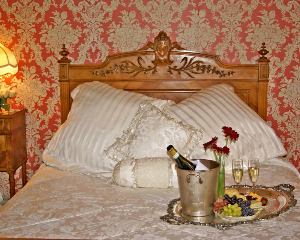 Ivory and gold covered bed topped with a silver platter of fruit, cheese, and champagne