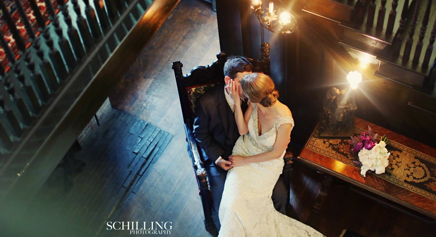 Bride sitting on grooms lap in tall wood chair in dimly lit room surrounded by dark trim, floors and stairs