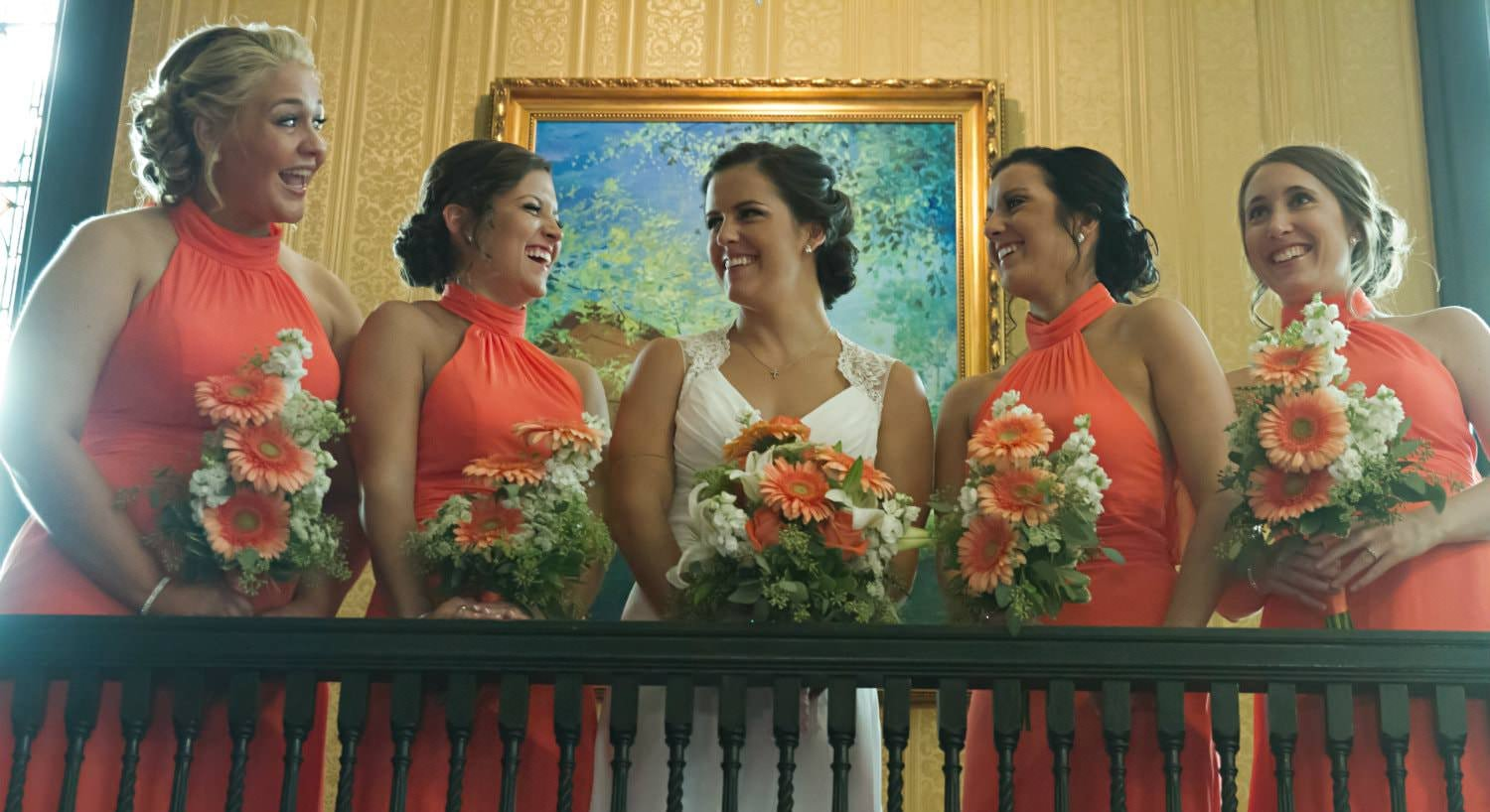 Bride in white dress flanked by two bridesmaids on each side in orange dresses all holding white and orange bouquets