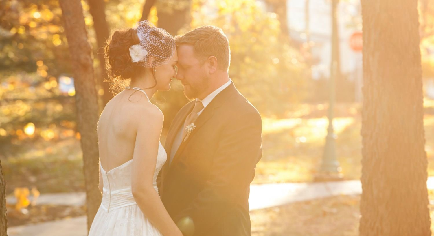 Bride in white dress holding hands, head to head with groom with diffused light and autumn trees in background