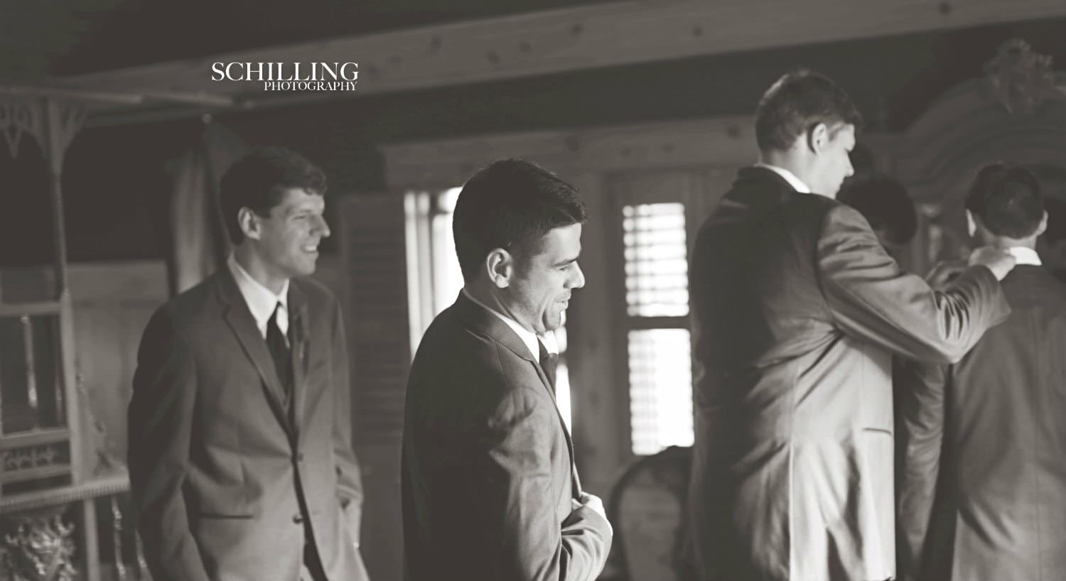 Black and white photo of several men dressed suits preparing for a wedding