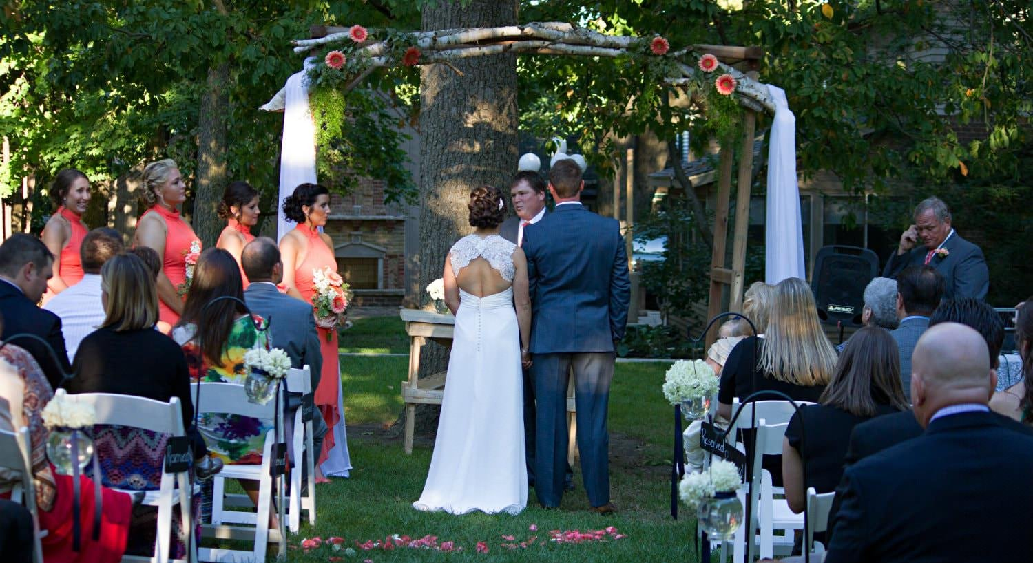 Bride and groom under homemade arch made of branches and white fabric getting married in front of friends and family