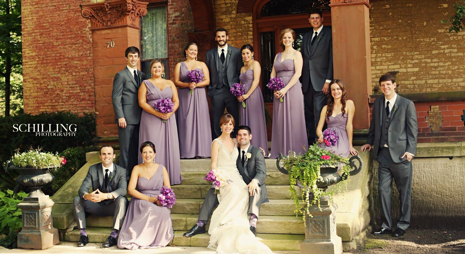 Bride and groom with five groomsmen in grey suits and five bridesmaids in purple dresses outside on the mansion steps