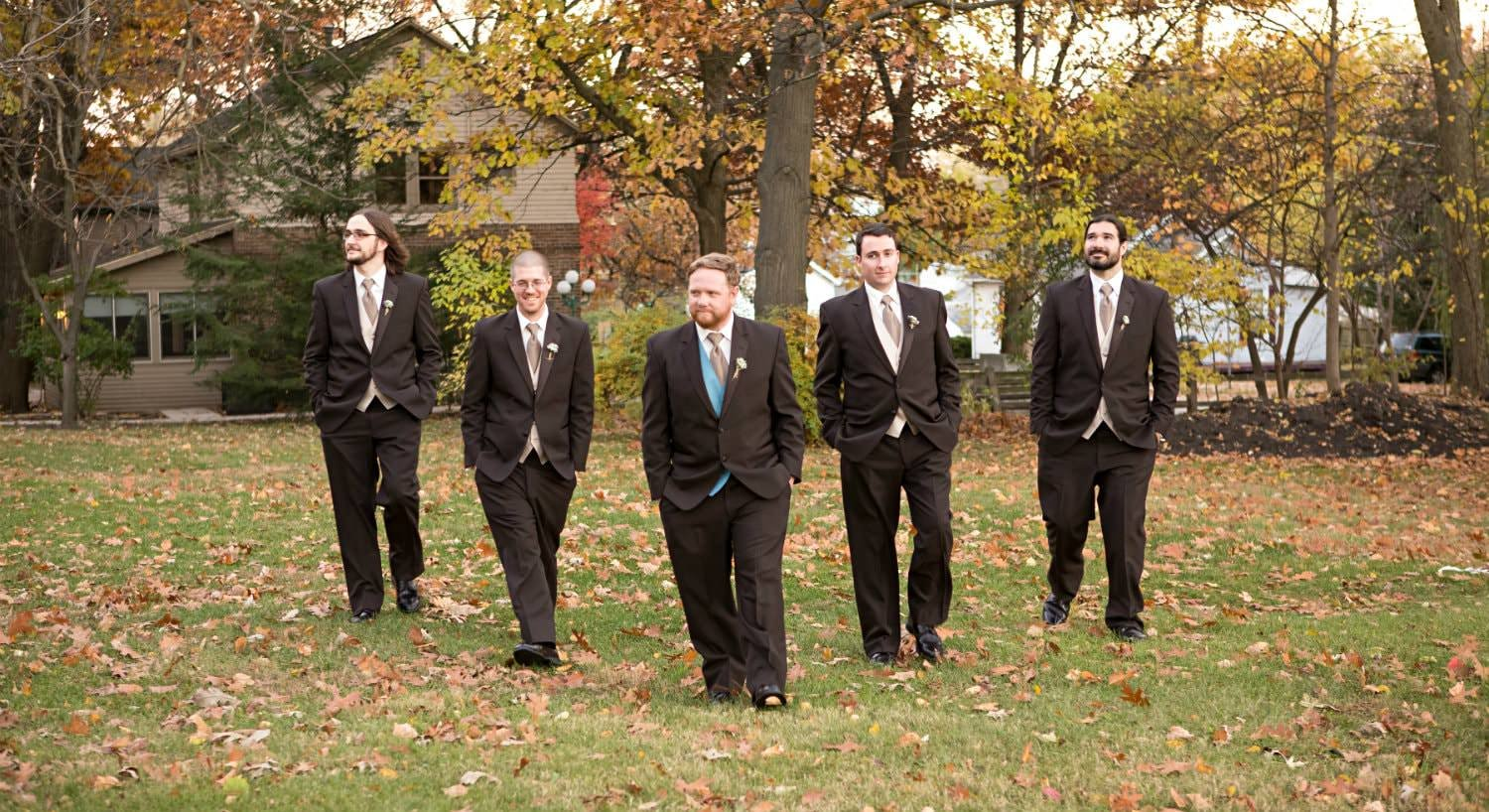 "Groom flanked by two groomsmen on each side walking in a ""v"" formation outside in the leaf-covered grass"