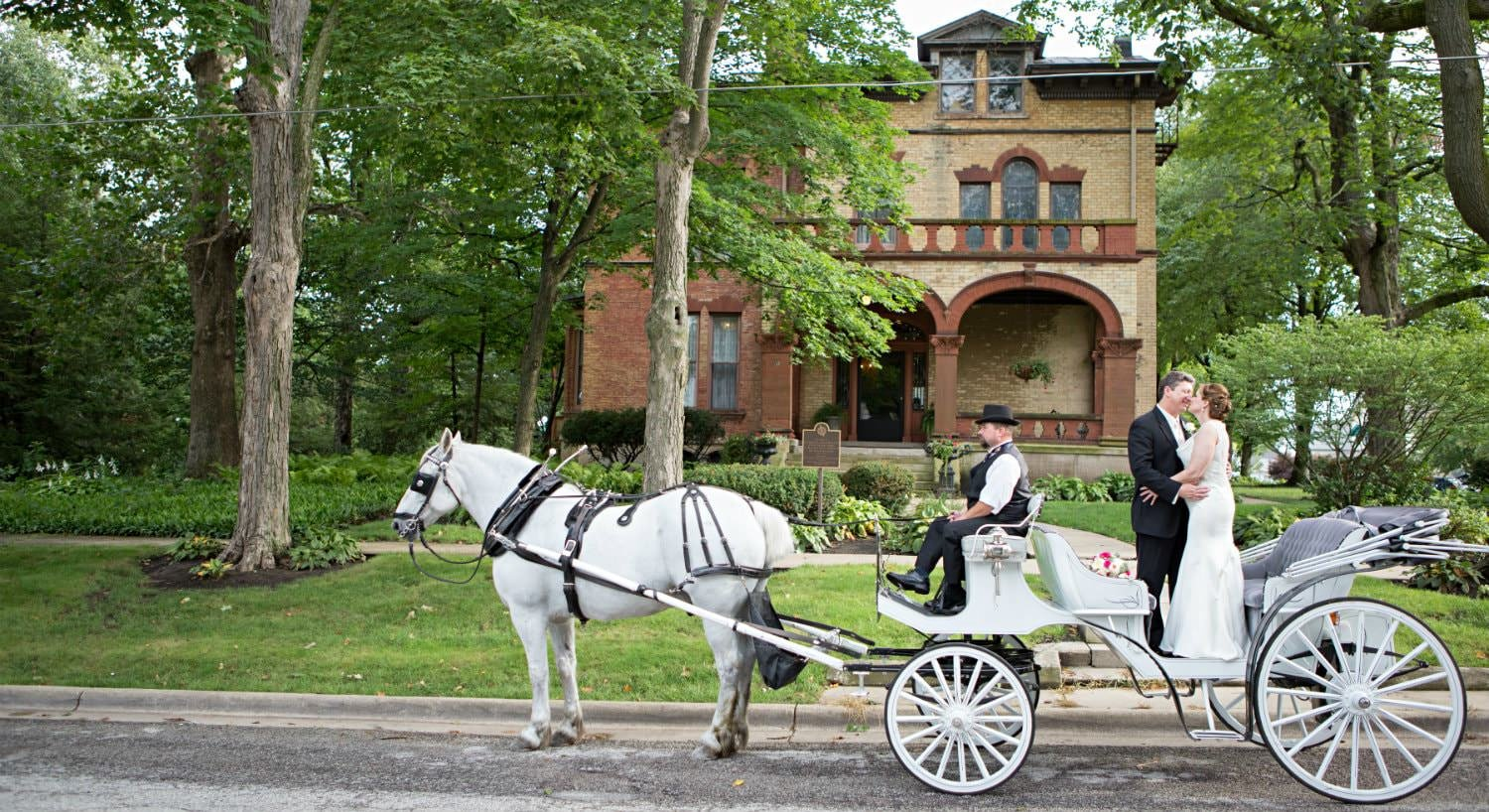 Bride and groom embracing in a white horse drawn carriage in front of the Vrooman mansion surrounded by green landscaping