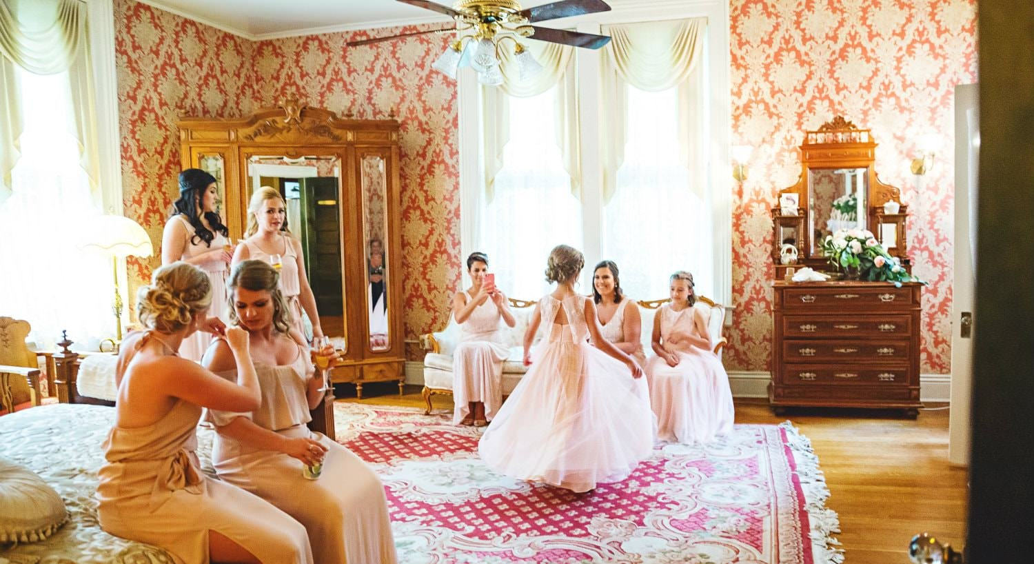 Brightly lit room with a bride in a white dress and several bridesmaids and flower girls in blush dresses