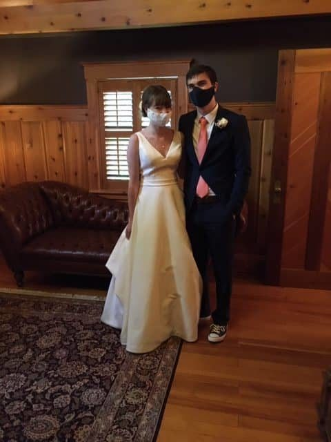 Bride in white dress wearing a white mask and groom in dark suit red tie wearing a black mask.
