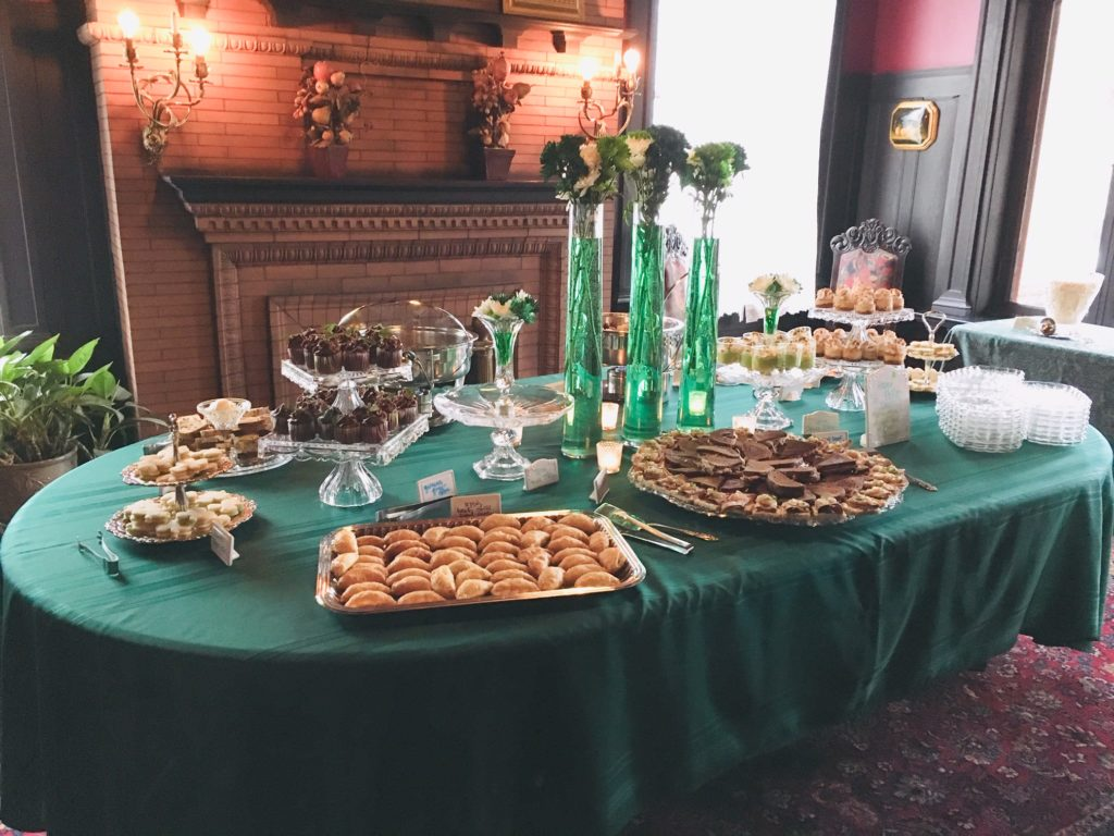 Dessert table with green tablecloth, set for Irish tea event