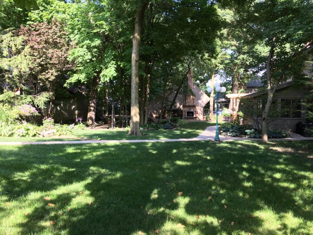 Shady back yard of Vrooman Mansion, with house visible through green, leafy trees