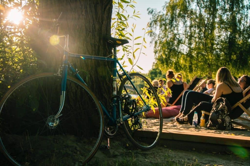 Bicycle leaning against tree with people sitting in folder chairs in sandy area right behind it.