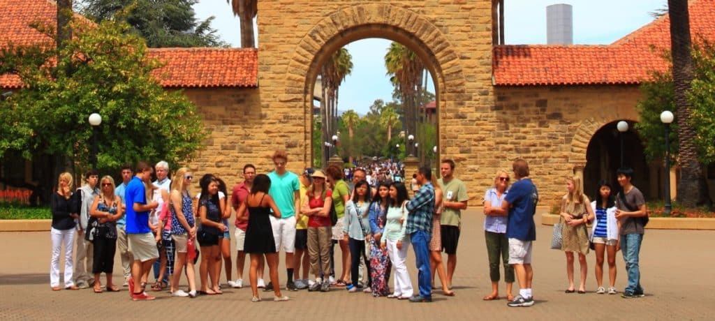 Group of people on college tour in front of arched outside gateway
