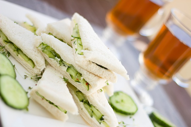 Plate of cucumber sandwiches on white bread, cut in triangles, with 2 cups of tea in clear mugs in the background