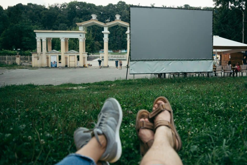 Foot (and shin) selfie of people lying on open lawn several yards from empty movie screen