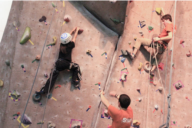 Two young men and a boy climbing a tall indoor rock wall