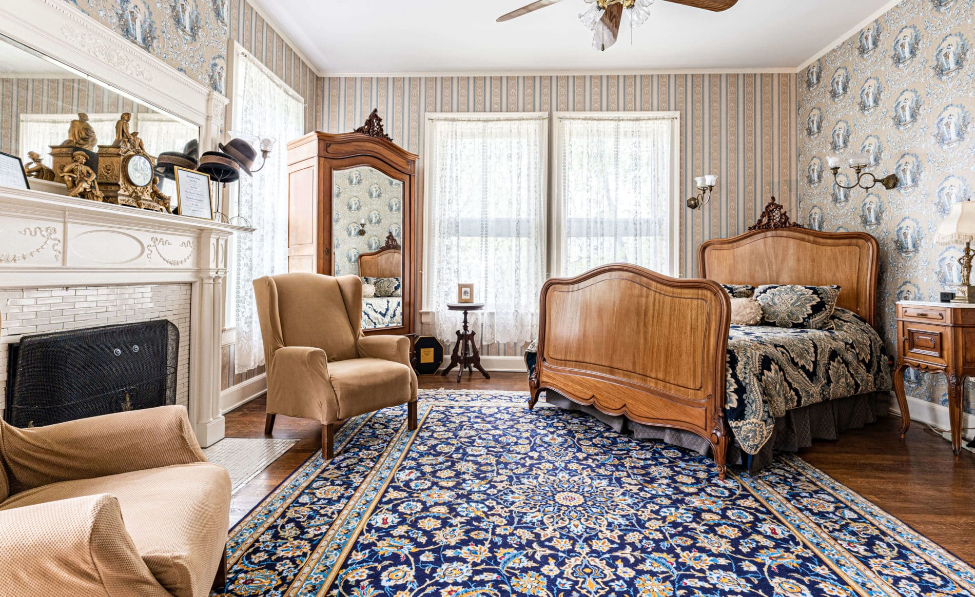 Julia's Room with a vibrant blue rug and antique headboard