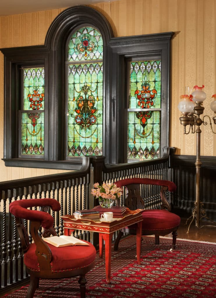 "Three stained glass windows, twins with oval-capped ""mother"" between them, from upstairs landing/parlor"