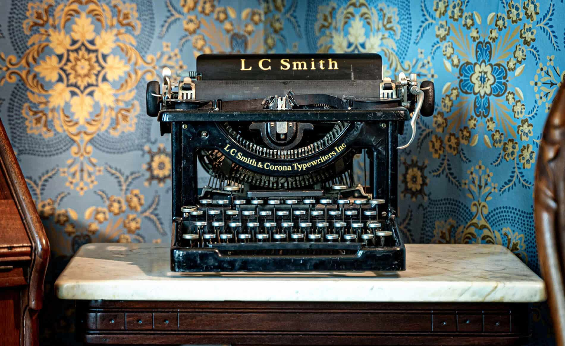 old-fashioned black typewriter with plate with text LC Smith & Corona Typewriters Inc sitting on marble topped walnut stand