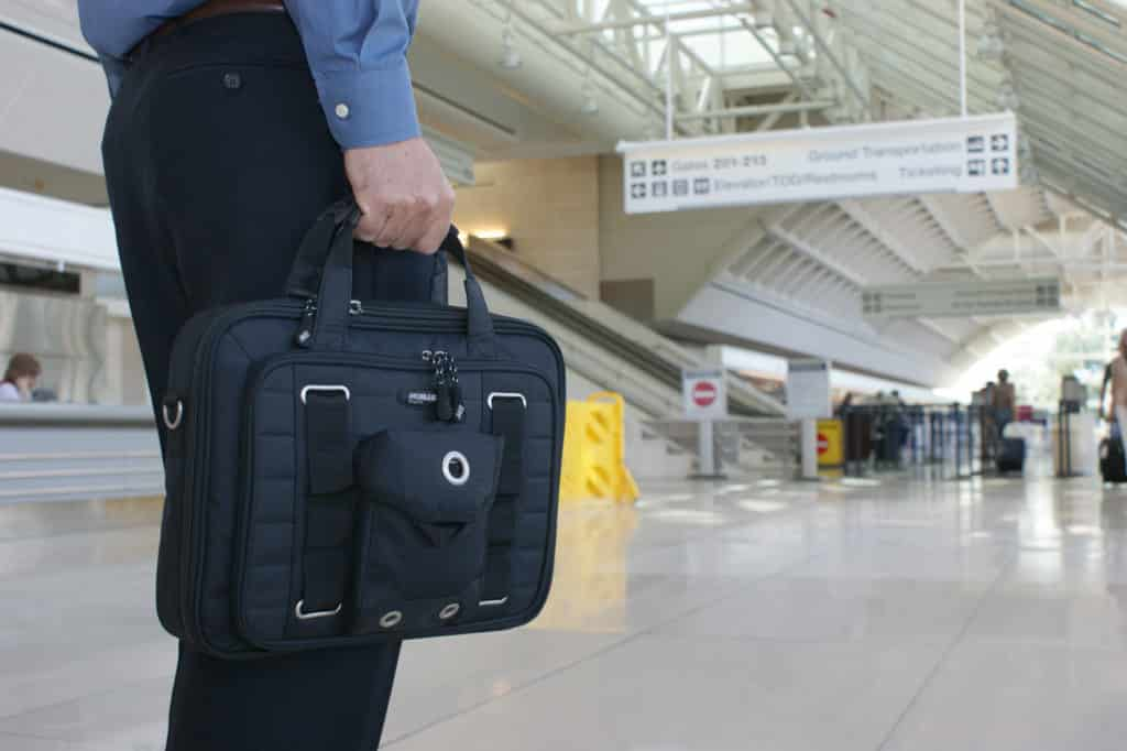 View of a man's hand holding a black briefcase walking through an airport