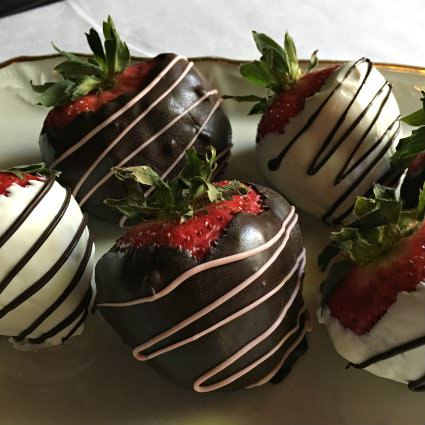 Red strawberries with green stems dipped in dark chocolate with pink drizzled icing and white chocolate with brown drizzled chocolateR