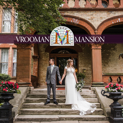 Bride in a white dress and groom in a dark gray suit standing close together, face to face